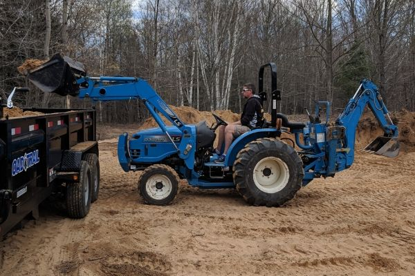 LS Tractor with FEL & Backhoe Loading Sand